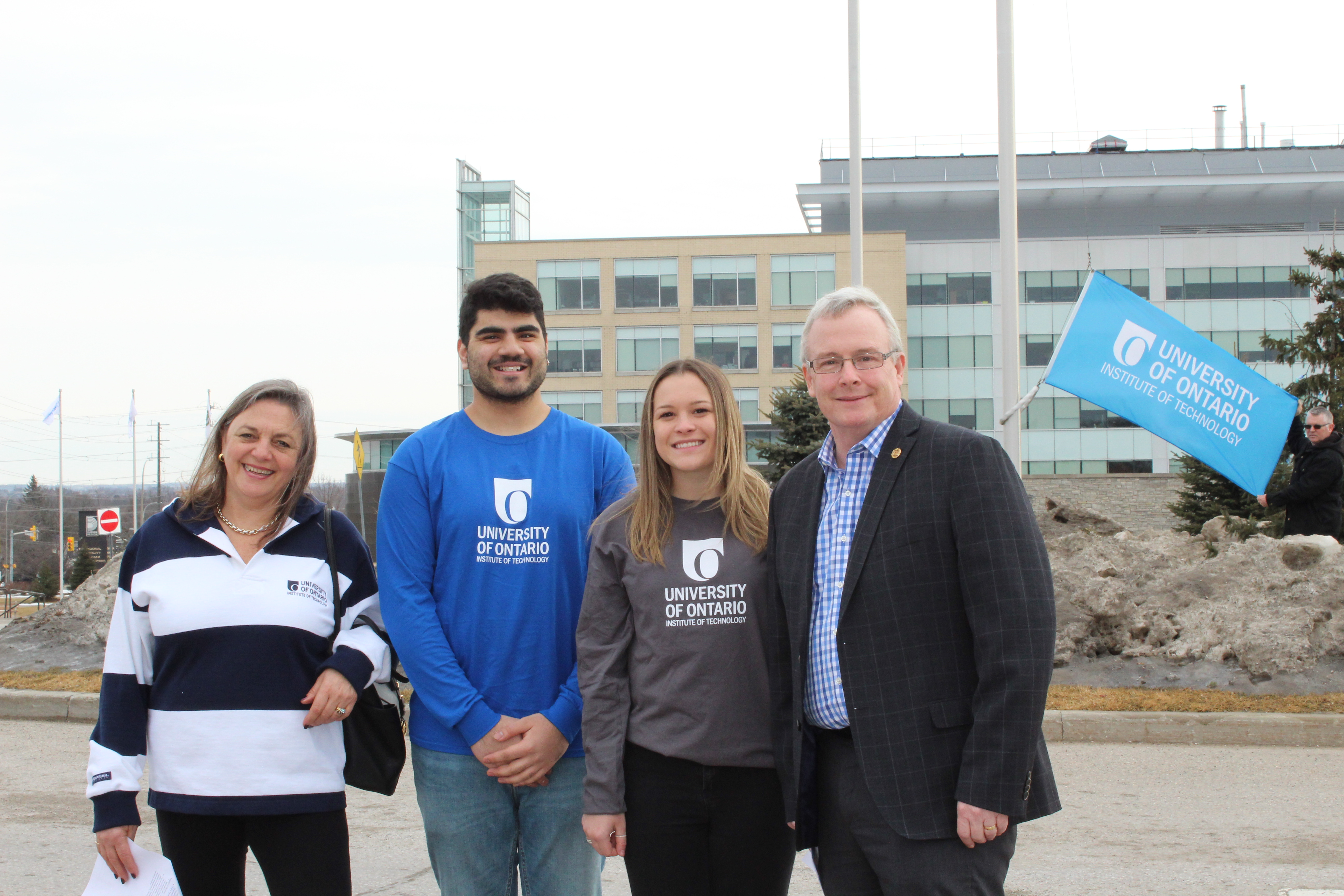 Susan McGovern, Moneel Lad, Samantha Pruden and Regional Chair John Henry raise the university's flag at the Region of Durham office.