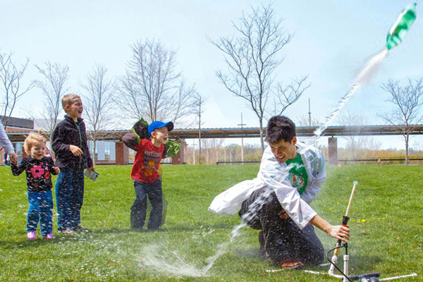 Volunteer at Science Rendezvous firing off a bottle rocket as excited kids watch