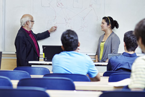 Student and professor using whiteboard in classroom