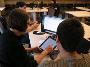 students working on a tablet and computer