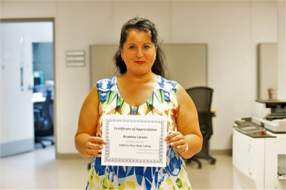 Volunteer note taker holding a certificate of achievement