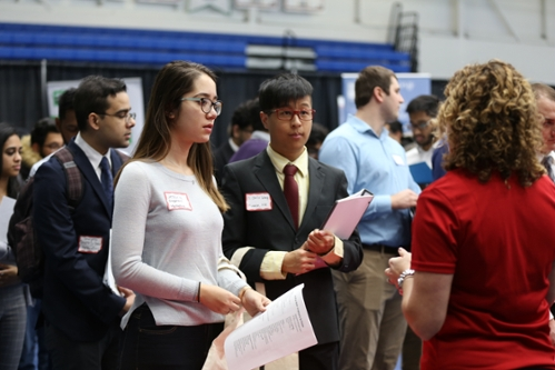 Students speaking with a company representative at the Job Fair