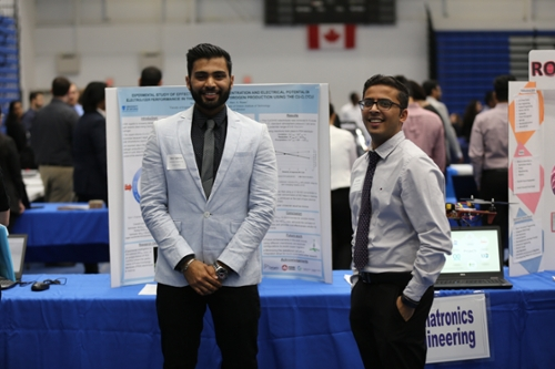 Engineering students standing in front of their display at a Reverse Career Fair. at the reverse career fair