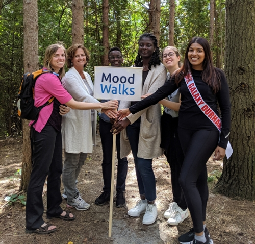 "Group of students and staff standing in nature around a sign that says ""Mood Walks"""
