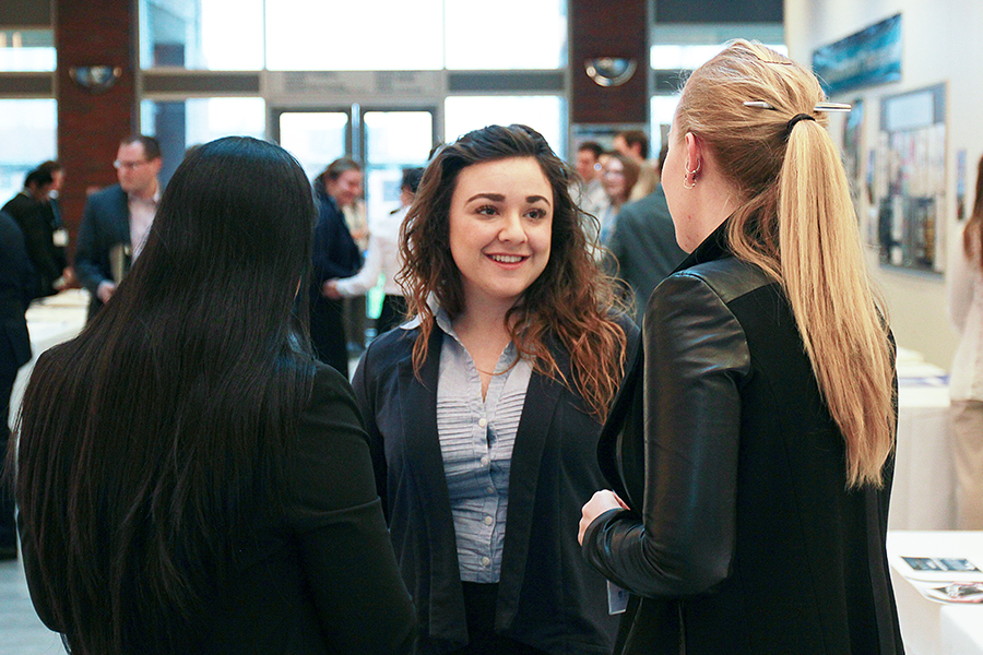 students talking to a representative at an event provided by the career services at the university