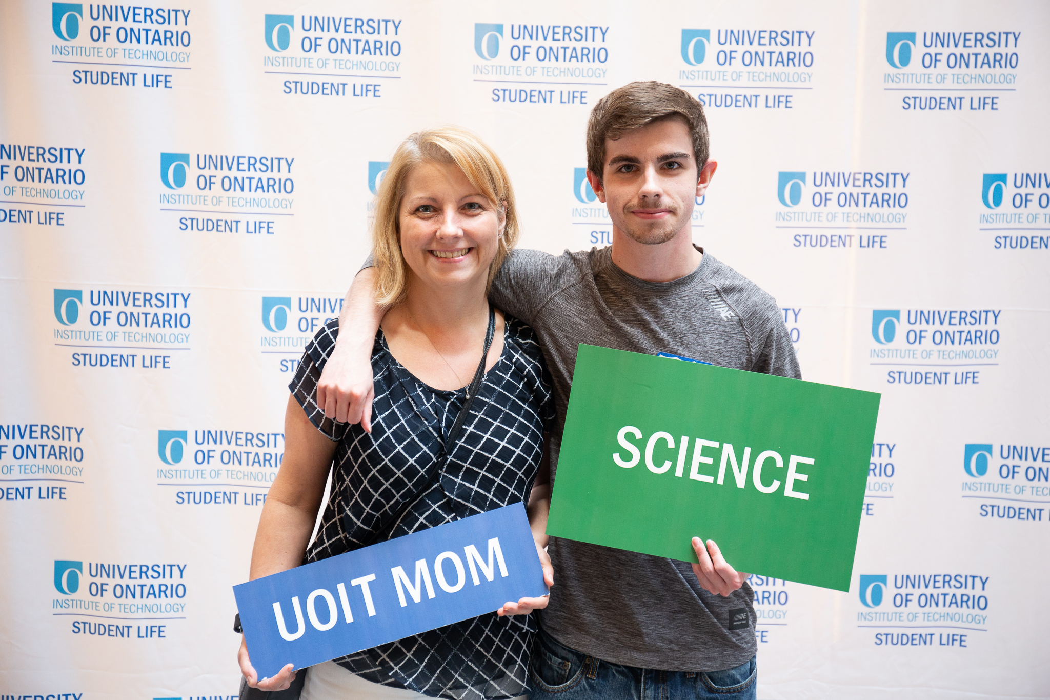 Student and mother holding science and uoit mom signs