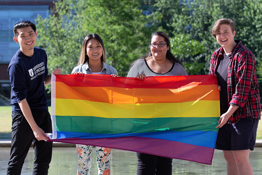 Students holding the LGBT+ (rainbow) flag