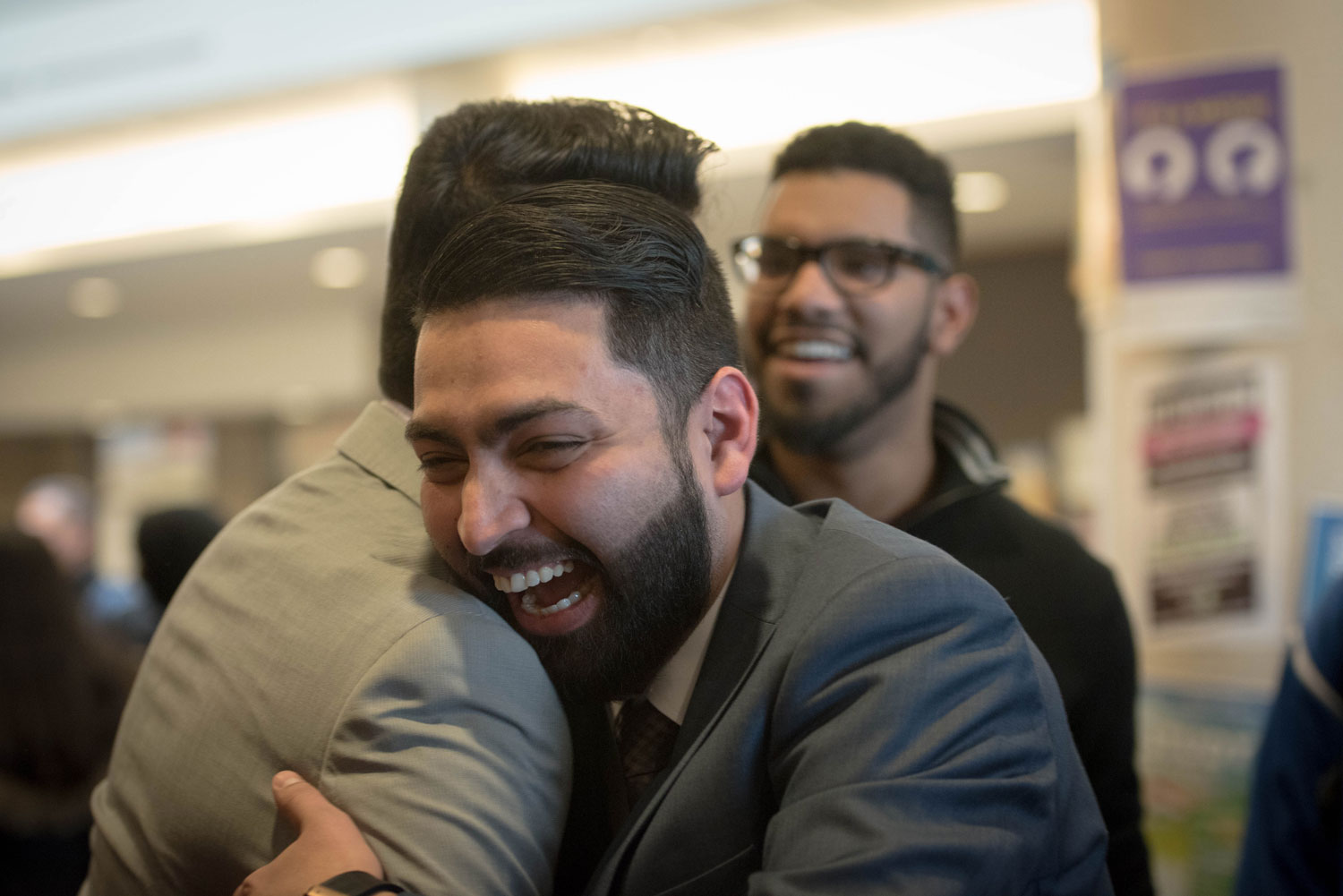 Colleagues share a joyful moment at the ceremony. ${altNumber}