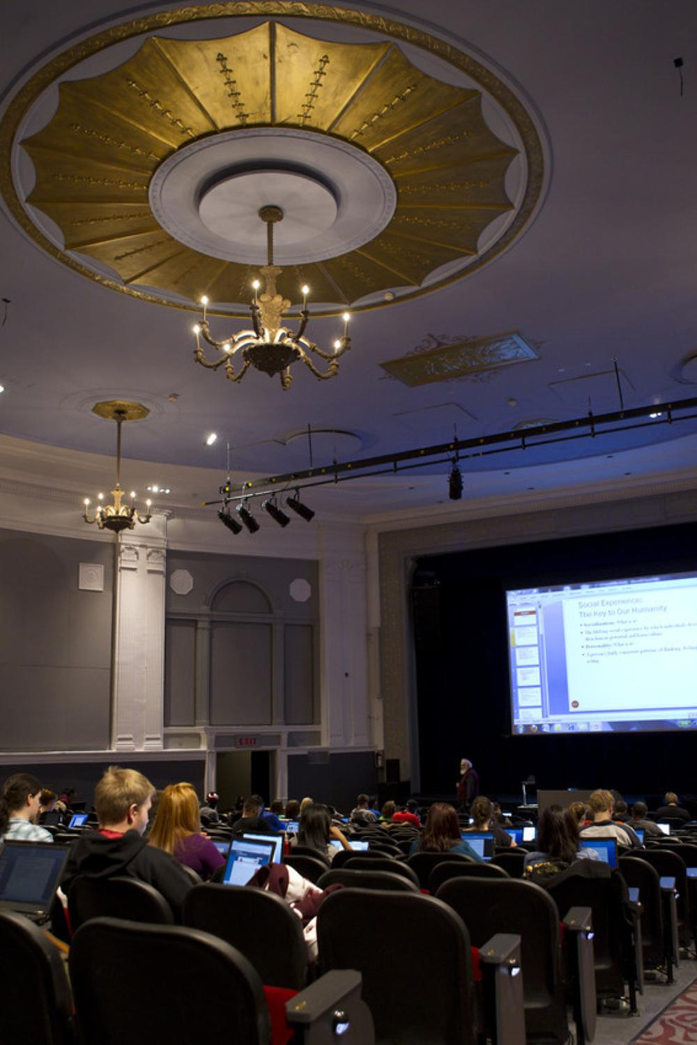 A lecture at the Regent Theatre.  Some students are on laptops.