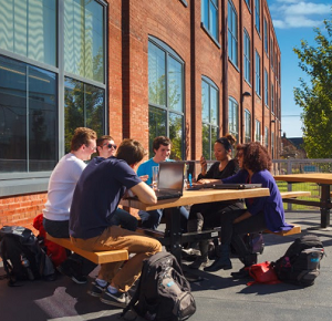 A group of students working at a table outside a campus building.