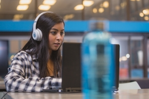A student wearing headphones sits in front of a laptop.