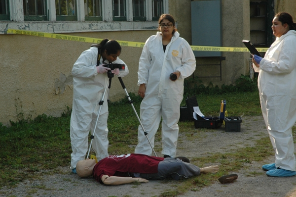 Forensic science students taking notes and photographs of a mock crime scene.