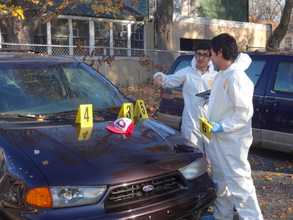 Forensic science students processing vehicle evidence during a laboratory.