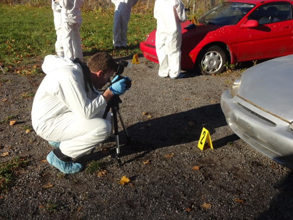 Forensic science student photographing a mock crime scene involving a vehicle.
