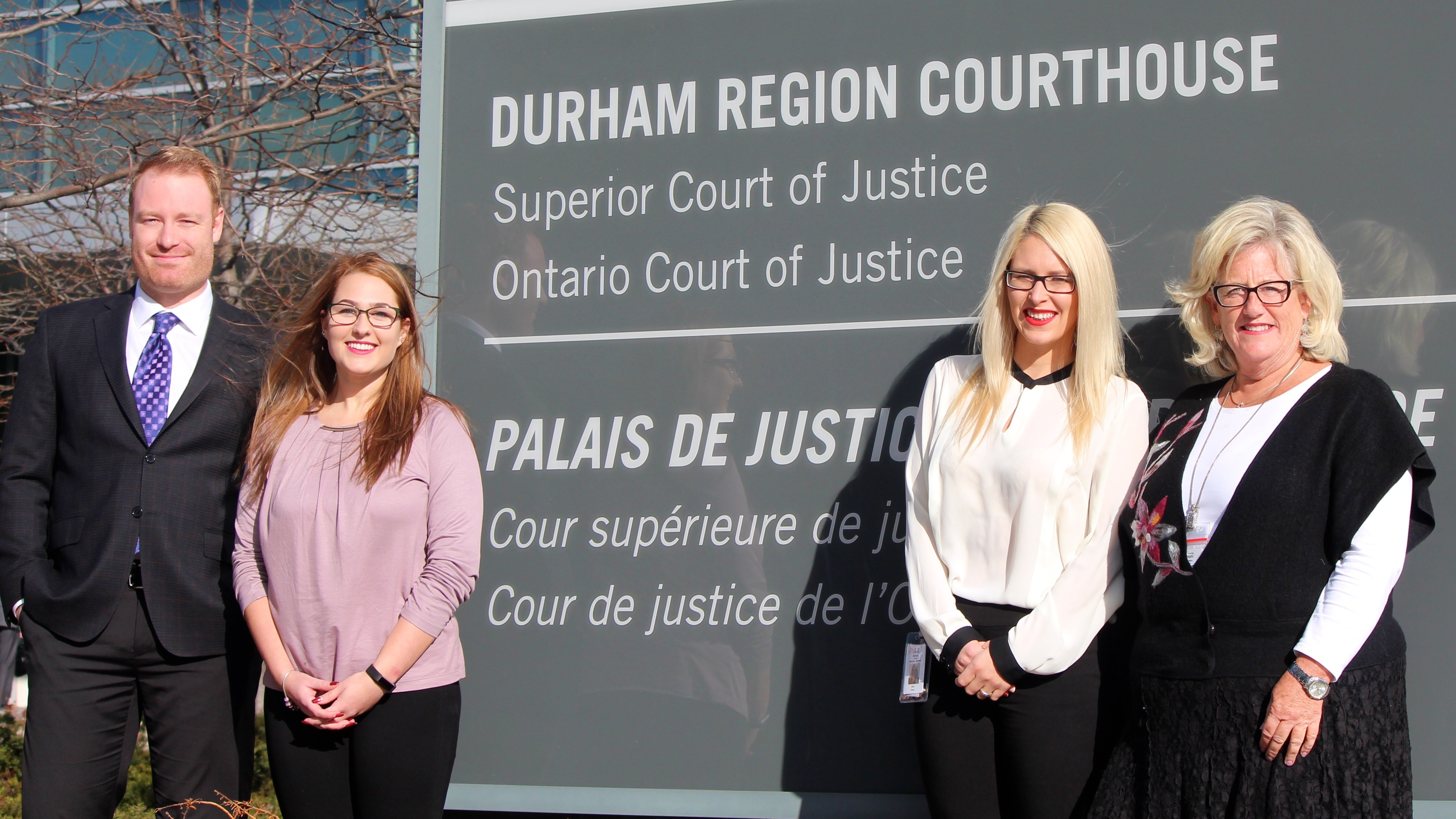Practicum student and staff standing at the courthouse