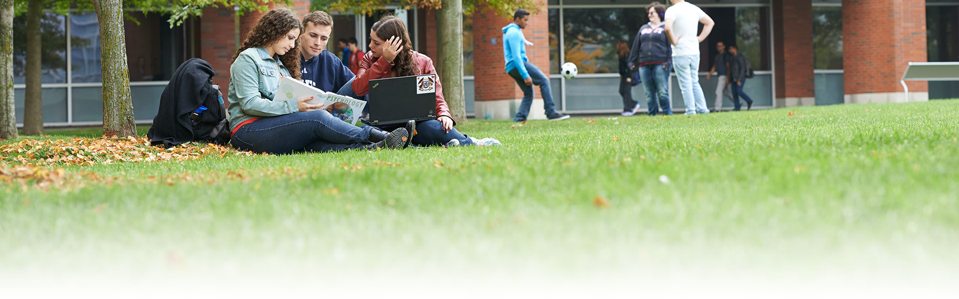 Students sitting outside UOIT building.