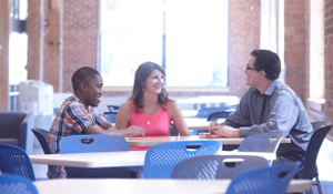students sitting around a table in a common area