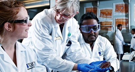 Researchers in white labcoats conducting research collaboratively